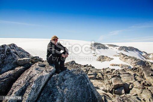 Hiker sitting in front of Folgefonn glacier in Norway