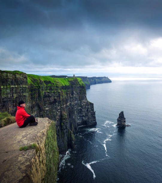 Hiker sitting at the cliffs of Moher stock photo