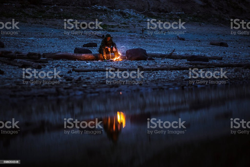 Hiker sitting near camping fire at river shore. Concept of stock photo