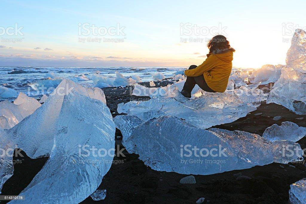 Hiker Sitting on Iceberg at Icy Jokulsarlon Coast in Iceland stock photo