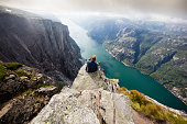 Hiker sitting on Kjeragnasen over Lyseford in Norway taking pictures with smartphone