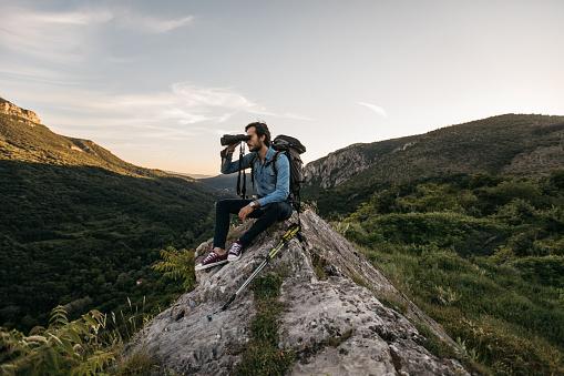 Hiker sitting on rock looking through binoculars