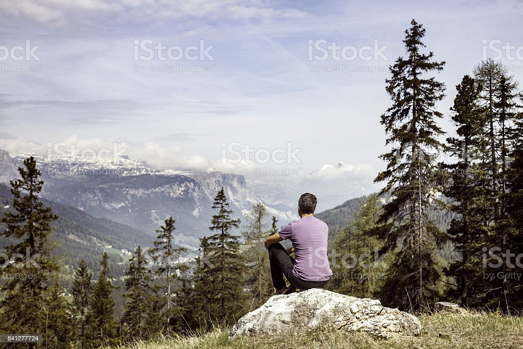 Hiker sitting on rock on mountain top in alpine landscape stock photo
