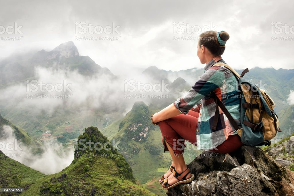 Hiker sitting on top of mountain enjoying on view of foggy mountains. stock photo