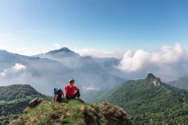 wandelaar zit op de top van berg - lecco lombardije stockfoto's en -beelden