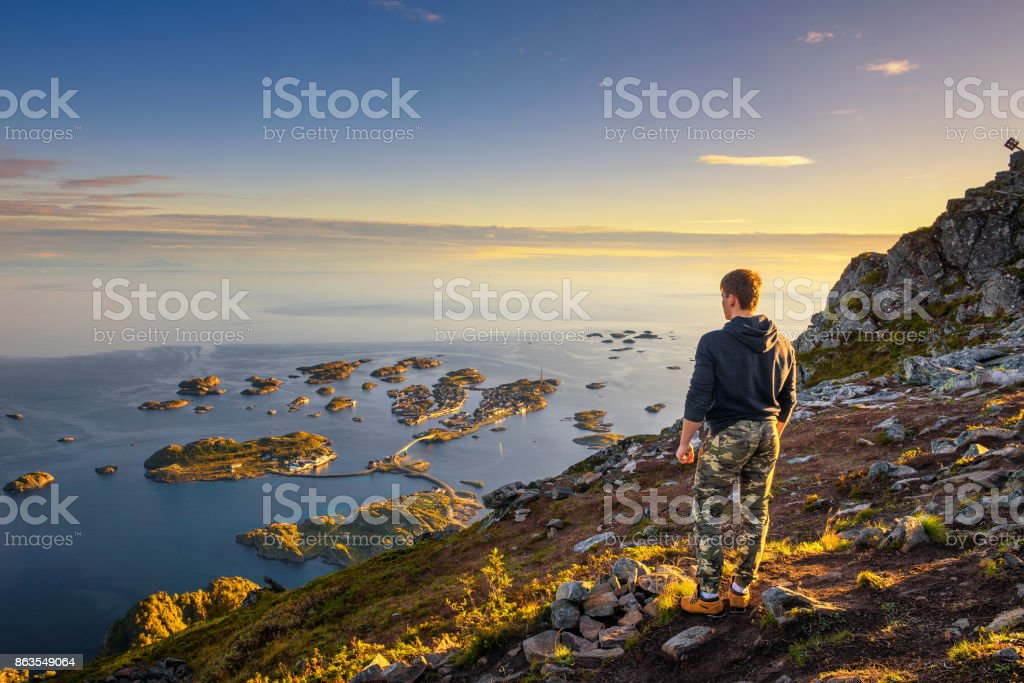 Hiker standing at the top of mount Festvagtinden on Lofoten islands in Norway stock photo