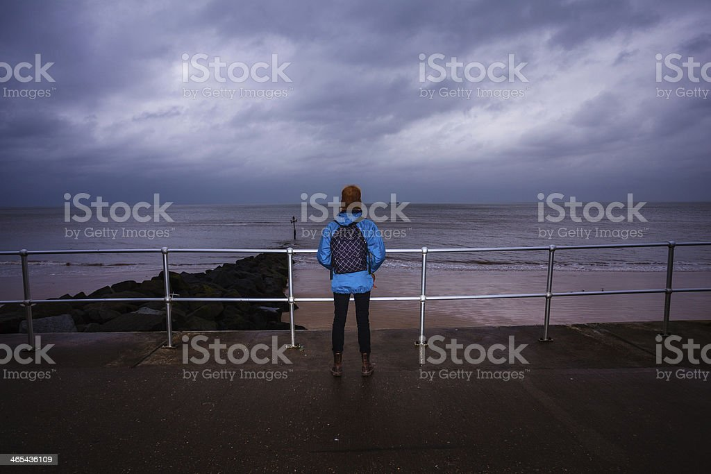 Hiker standing by the sea on a stormy day stock photo
