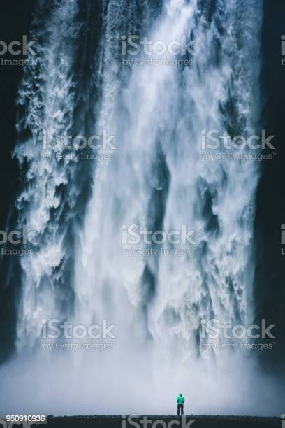 Photo of Hiker standing in front of gigantic Skogafoss waterfall in Iceland