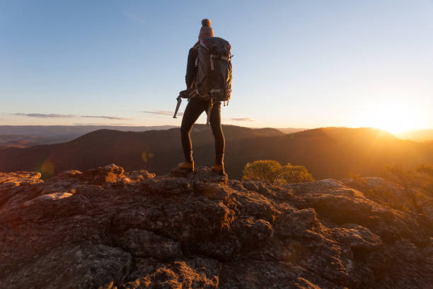 Hiker standing on cliff ledges mountain top Nothing can substitute experience.  Standing on the edge of Mt Victoria  as the golden sun dips low on the horizon mt victoria canadian rockies stock pictures, royalty-free photos & images