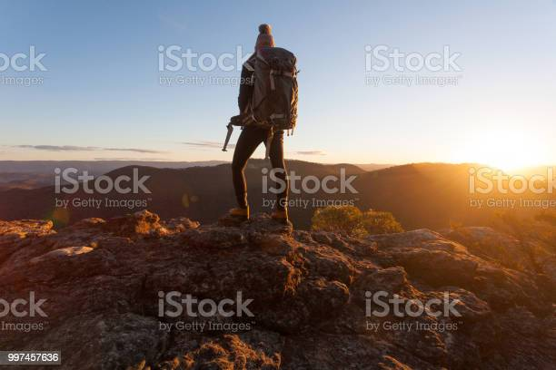 Photo of Hiker standing on cliff ledges mountain top