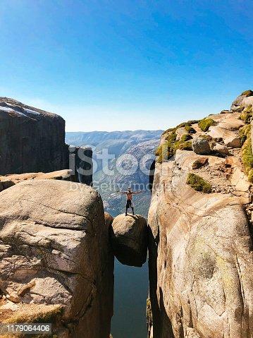 Hiker standing on Kjeragbolten in Norway
