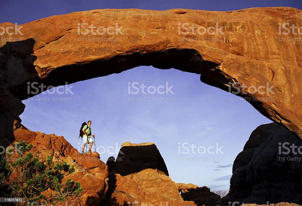Hiker Standing On Massive Rock Under Arch In Utah royalty-free stock photo