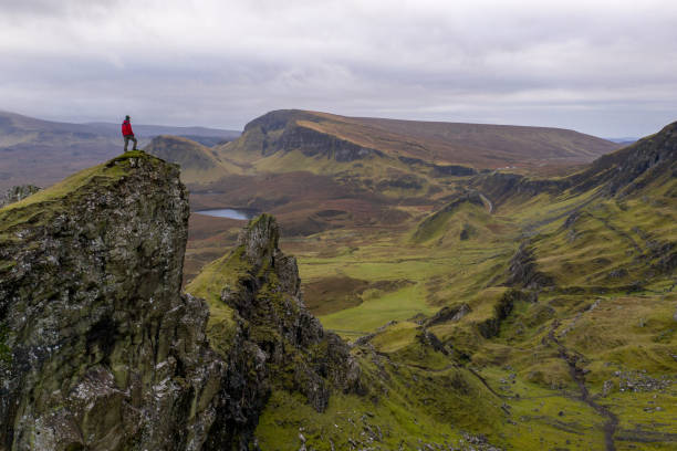 Hiker standing on mountain top in rugged volcanic landscape around Old Man of Storr, Isle of Skye, Scotland Hiker standing on mountain top in rugged volcanic landscape around Old Man of Storr, Isle of Skye, Scotland isle of skye stock pictures, royalty-free photos & images