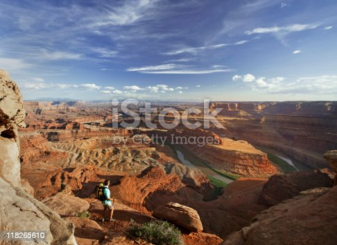 High angle view of backpacker standing on rocky ledge admiring magnificent view of canyons in Canyonlands National Park.