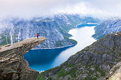 Female hiker standing on Trolltunga (troll tongue) famous rock high above a lake with panoramic view of the valley, popular tourist adventure trek in Norway
