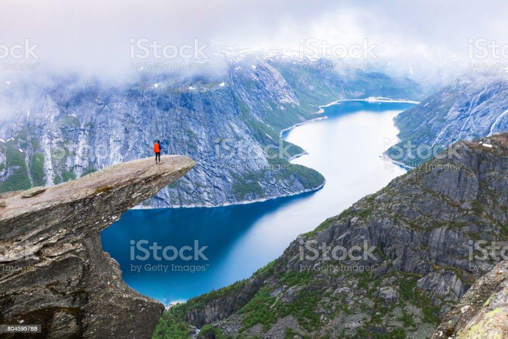 Excursionista de pie en Trolltunga con vista panorámica del lago, Noruega - foto de stock
