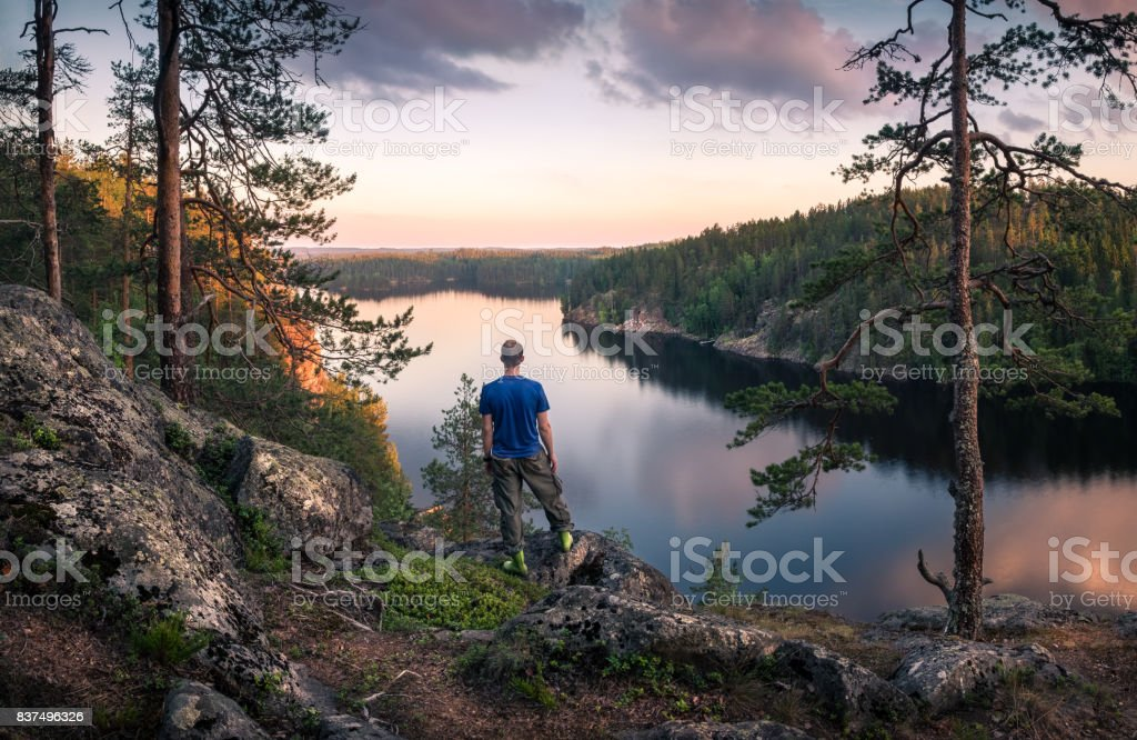 Hiker standing top of the hill front of beautiful idyllic landscape stock photo