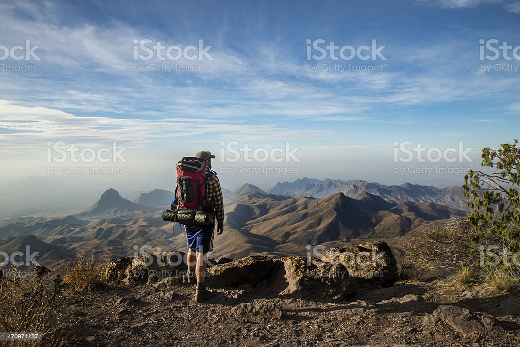 Hiker Stands on a Cliff stock photo