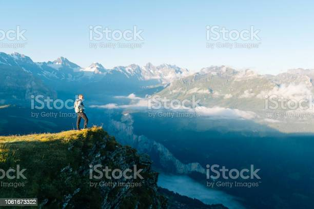 Photo of Hiker stands on mountain meadow crest