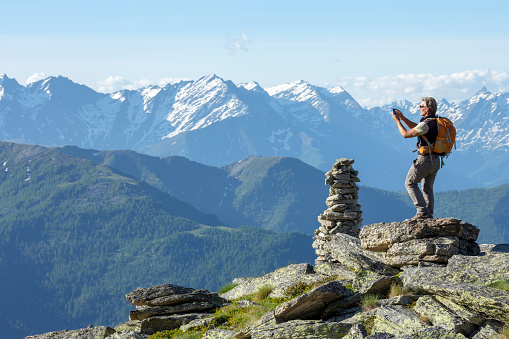 Hiker takes photo on sunny mountain summit by rock cairn