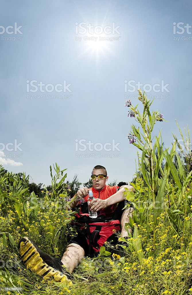Hiker taking a brake in the field royalty-free stock photo