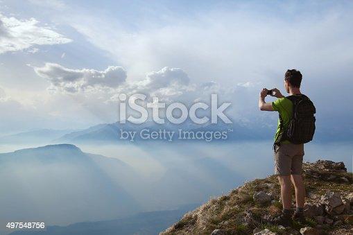 istock hiker taking photo of beautiful mountain landscape 497548756