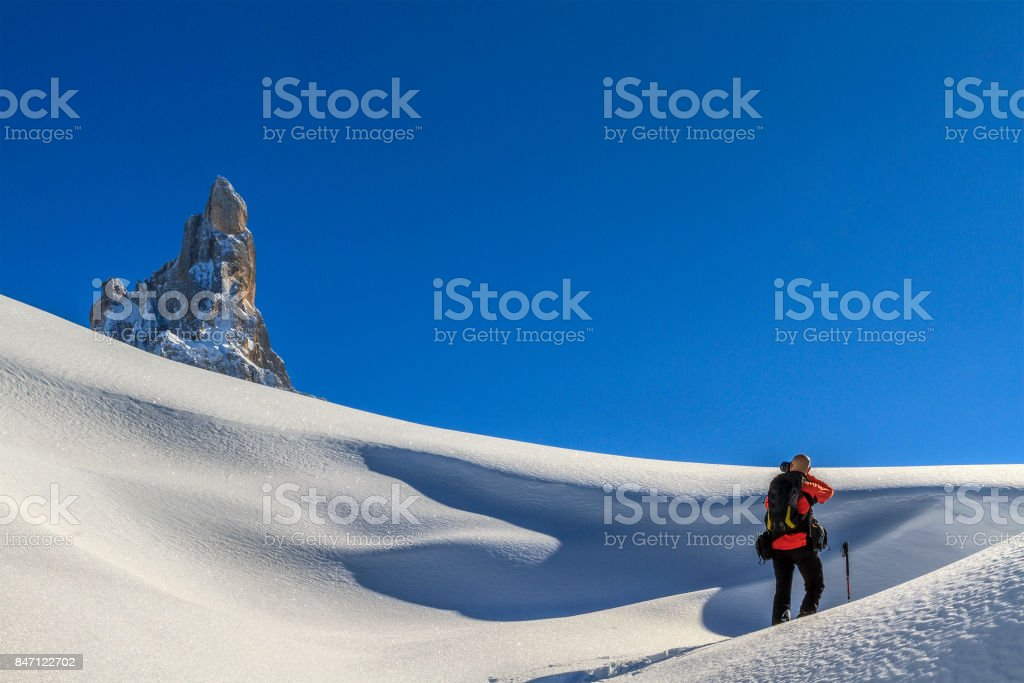 Hiker taking picture in the Pale di San Martino Natural Park in winter, Italy stock photo