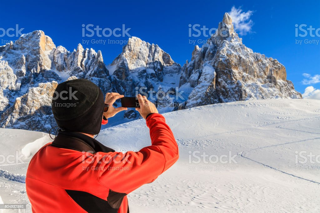 Hiker taking picture with phone in the Pale di San Martino Natural Park in winter, Italy stock photo