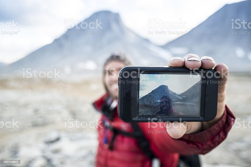Hiker taking selfie with mountains in background stock photo