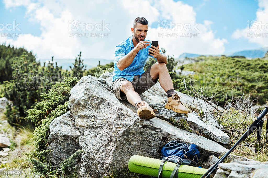 Hiker texting on a big rock stock photo