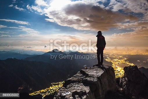 Hiker on top of the mount at night, in the valley town lighted
