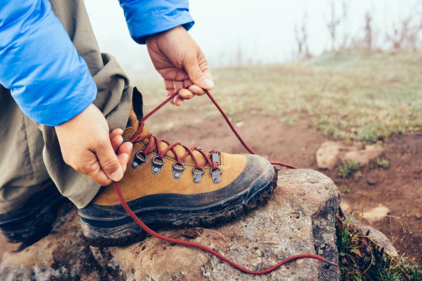 Wanderer, die Schnürsenkel zu binden, auf nebelige Highland mountain – Foto