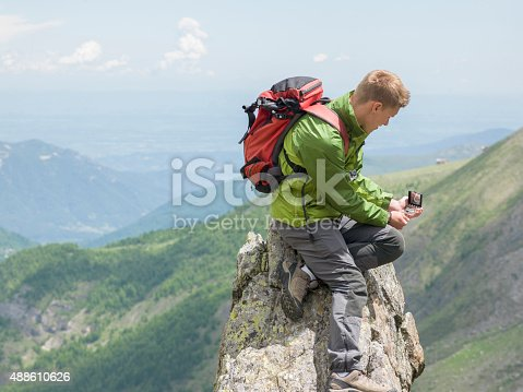 Hiker uses compass for direction finding, mountains