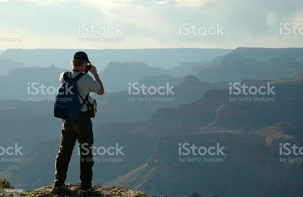 Hiker using binoculars to view canyon stock photo