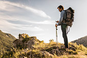 Hiker using compass on mountain