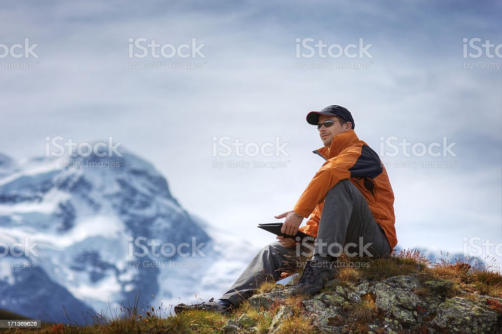 Hiker Using Digital Tablet in the Mountains royalty-free stock photo
