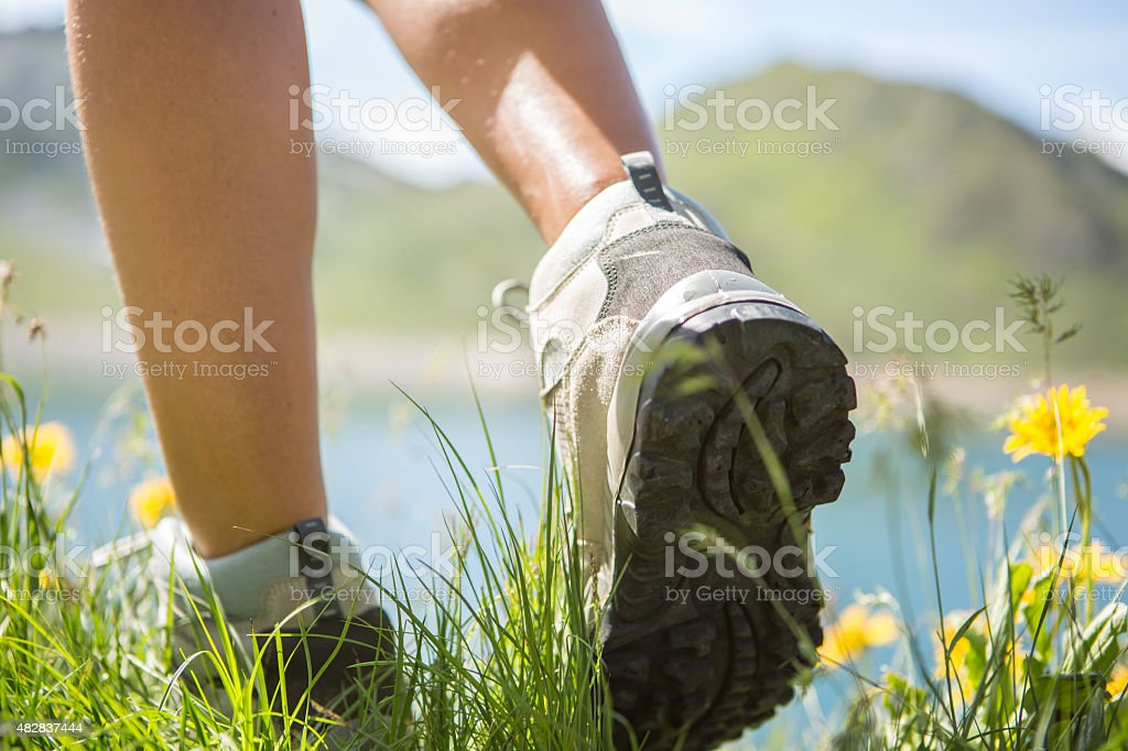 Hiker walk on a mountain trail-Close up on boots stock photo