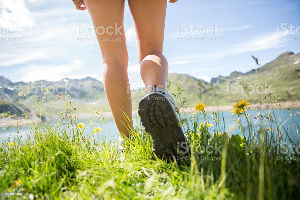 Hiker walk on a mountain trail-Close up on boots-Summer stock photo