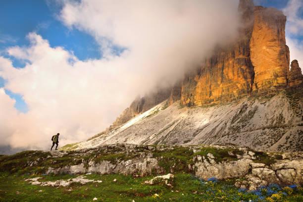 Hiker walk under the mountains Tre Cime di Lavaredo National Park, Dolomites, European Alps, Italy, stock photo