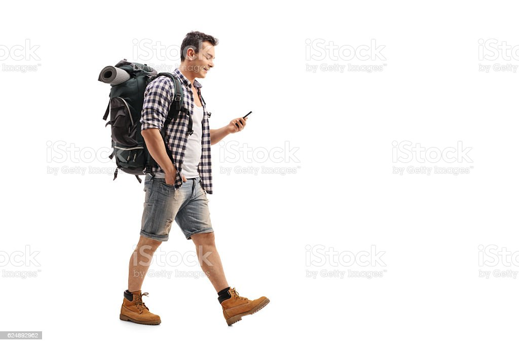 Hiker walking and looking at a mobile phone – Foto