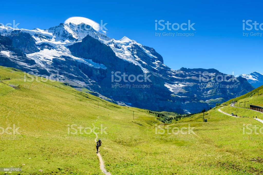 Hiker walking in beautiful mountain scenery at Grindelwald and Jungfrau - Switzerland stock photo