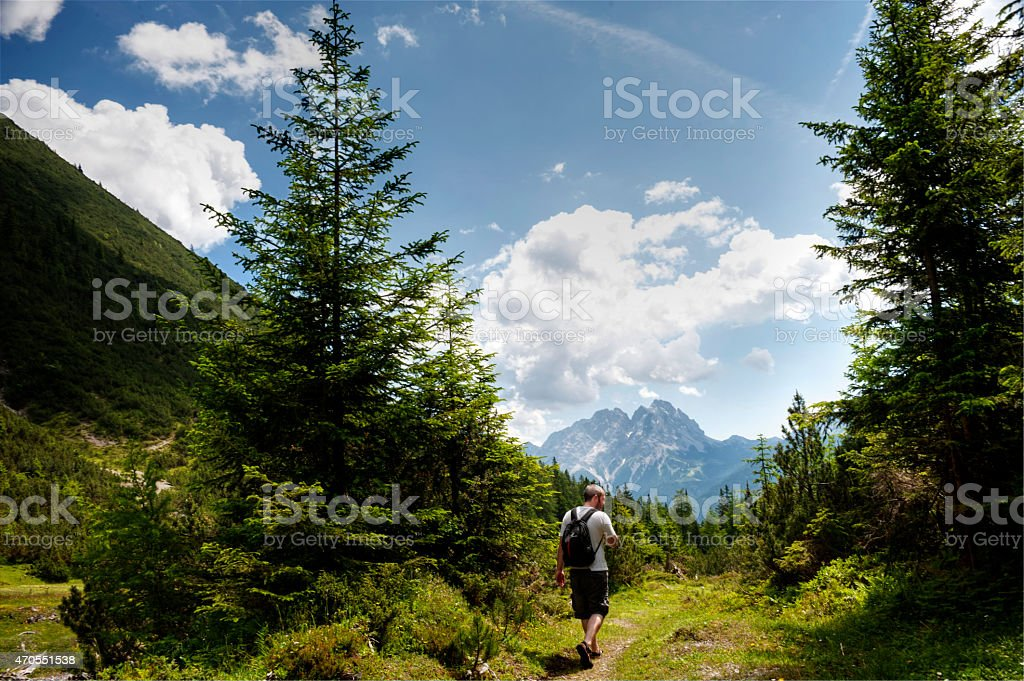 Hiker walking on a dirt track stock photo