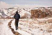Backpacker walking alone in the winter on the beautiful hills of the \
