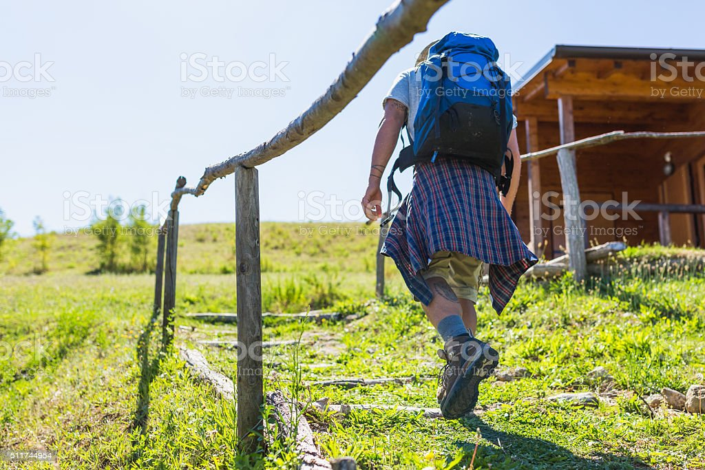 Hiker walking on country trail to arrive to his cottage stock photo