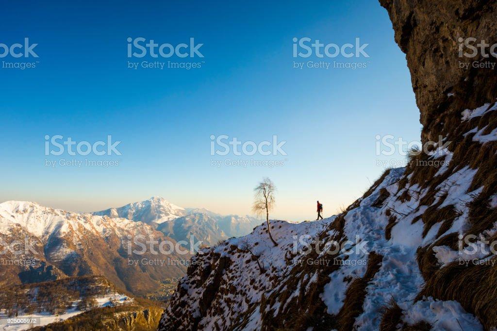 Hiker walking on mountain path stock photo