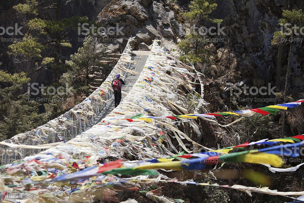 Hiker walking on suspension bridge in Nepal royalty-free stock photo