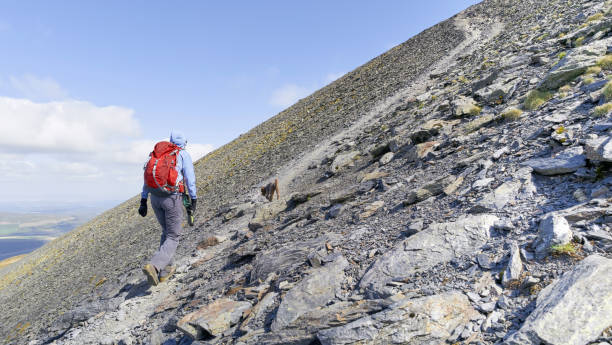 A hiker walking up a steep rocky mountain trail. A hiker walking up a steep rocky mountain trail leading to the summit of Skiddaw in the English Lake District. steep stock pictures, royalty-free photos & images