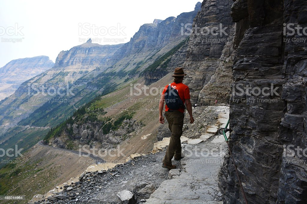 Hiker walks a narrow path stock photo