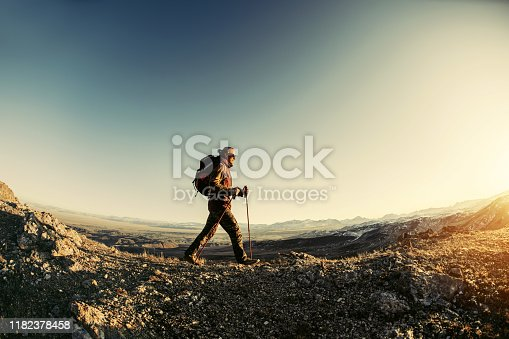 Hiker walks with backpack and trekking poles in sunset mountains