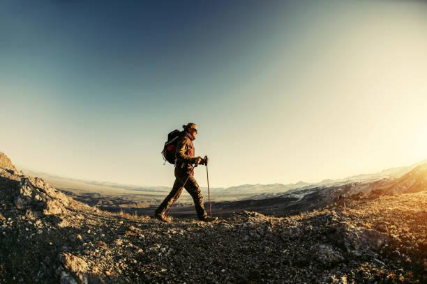 Hiker walks in sunset mountains